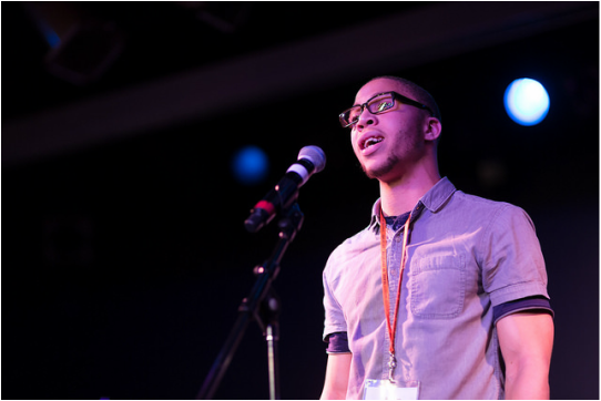Picture of African American young man with glasses standing at a mic speaking