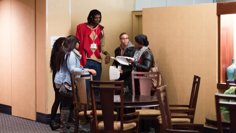 Picture of students gathered around a table working together