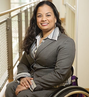 Head shot of Dr. Anjali Forber-Pratt, a light brown-skinned woman with long, dark wavy hair, a smile, and a gray suit jacket and gray-and-white striped shirt.