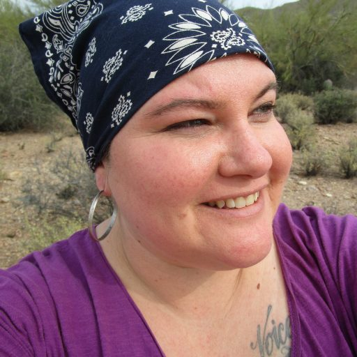 Headshot of Naomi Ortiz, a Metiza (indigenous / Latina / white). She is wearing a navy-and-white patterned bandana, a purple shirt, and silver hoop earrings. With shrubs and plants of a southwest desert landscape behind her, Naomi smiles, squinting as she looks off to the side.
