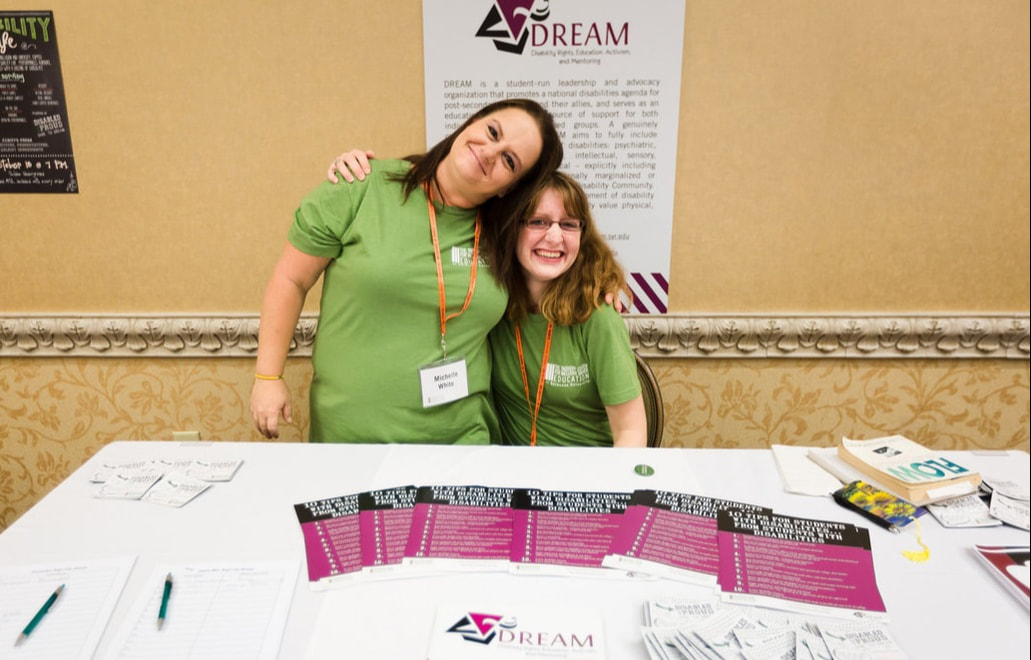 Two young white women, one standing and one sitting, each wear green shirts and have a conference name badge hanging around their necks. They are smiling and each has an arm around the other. One the wall behind them is a DREAM poster and on the table in front of them are various publications and pens with the DREAM logo on them.