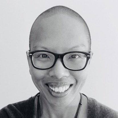 Headshot of liz thompson, a brown person with close-cut dark hair and black rimmed glasses and wearing a dark tee and sweater