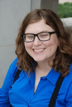Headshot of Val Erwin, a white woman with shoulder-length wavy  brown hair and dark-rimmed eyeglasses. Val is smiling and wearing a royal blue button-down shirt with black suspenders.